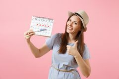 Excited happy woman in blue dress, hat hold in hand pregnancy test, periods calendar for checking menstruation days. Isolated on pink background. Medical stock image