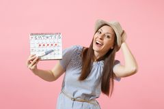 Excited happy woman in blue dress, hat hold in hand pregnancy test, periods calendar for checking menstruation days. Isolated on pink background. Medical stock photography