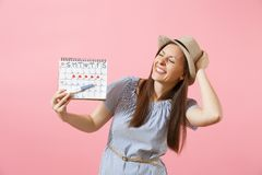 Excited happy woman in blue dress, hat hold in hand pregnancy test, periods calendar for checking menstruation days. Isolated on pink background. Medical stock photos