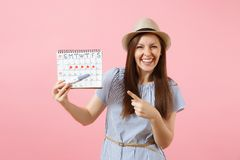 Excited happy woman in blue dress, hat hold in hand pregnancy test, periods calendar for checking menstruation days. Isolated on pink background. Medical royalty free stock image