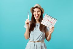 Excited happy woman in blue dress, hat hold in hand pregnancy test, periods calendar for checking menstruation days. Isolated on blue background. Medical stock image