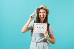 Excited happy woman in blue dress, hat hold in hand pregnancy test, periods calendar for checking menstruation days. Isolated on blue background. Medical stock photography