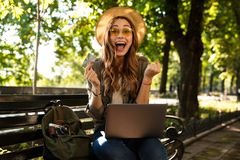 Excited happy woman outdoors sitting using laptop computer. royalty free stock image