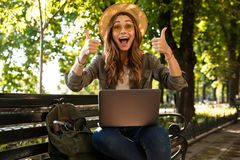 Excited happy woman outdoors sitting using laptop computer make thumbs up. royalty free stock images