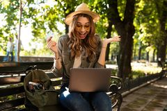 Excited happy woman outdoors sitting using laptop computer. royalty free stock photos