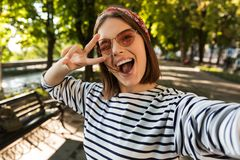Excited happy woman outdoors take a selfie by camera showing peace gesture. royalty free stock photography