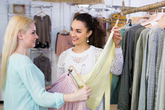 Excited happy women shopping pullover and skirt at the apparel s. Tore Royalty Free Stock Photos
