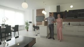 Excited happy young couple looking around interior kitchen trendy modern design moving in new apartment in 4k shot stock footage