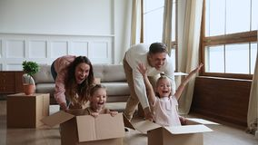 Parents and children homeowners playing with boxes on moving day