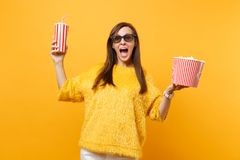 Excited happy young woman in 3d imax glasses watching movie film, holding bucket of popcorn and plastic cup of cola or. Soda isolated on yellow background royalty free stock image
