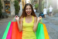 Excited happy young woman shows colorful shopper bags in Brera n royalty free stock photo
