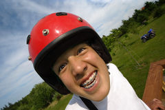 Excited helmet boy. An ecstatic Asian boy with red helmet, getting ready to ride an all terrain vehicle parked in the background Stock Images