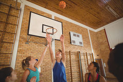Excited high school kids scoring a goal while playing basketball. In the court Stock Images