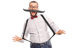 Excited hipster with fake mustache. Excited young male hipster with fake mustache and black suspenders isolated on white background royalty free stock image