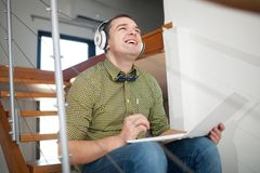Excited hipster man relaxing with music and laptop Royalty Free Stock Photos
