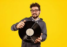 Excited hipster man with vinyl record and earphones Royalty Free Stock Photos