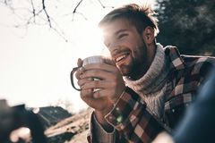 Excited about his adventure. Handsome young man in warm clothing. Having morning coffee and smiling while camping in mountains stock images