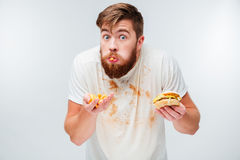 Excited hungry bearded man greedily eating hamburgers Royalty Free Stock Image