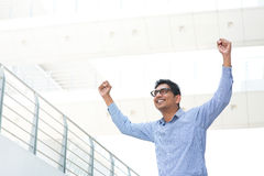Excited Indian business man. Successful Asian Indian businessman with arms up celebrating his victory, modern office building as background Stock Photography