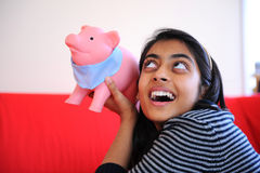 Excited Indian girl holding piggybank Royalty Free Stock Photos