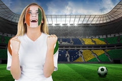 Excited ivory coast fan in face paint cheering Stock Photo