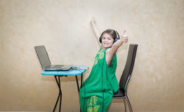 Excited joyful happy little girl celebrate her successful computer work Royalty Free Stock Photos