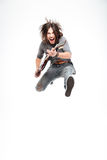 Excited joyful male guitarist with electric guitar shouting and jumping Royalty Free Stock Images