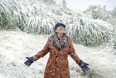 Excited joyful woman standing in falling snow for first time in life Stock Images