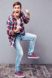 Excited joyful young man in checkered shirt and jeans dancing Royalty Free Stock Photography