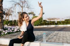 Excited joyful young woman in sportswear gratulating to side in sunny morning. Expressing positivity, sitting on street. Of tropical city, smiling, training royalty free stock images