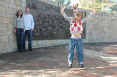 Excited Kid. Young little girl jumps in the air as her mom and dad watch behind her Royalty Free Stock Image