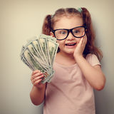 Excited kid girl earring money and thinking how spend its. Close Stock Photo