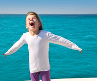 Excited kid girl sailing in a boat open arms Stock Images