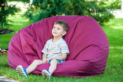 Excited kid having fun on bean bag at summer or sping park outdoors Royalty Free Stock Images