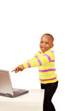 Excited kid pointing to computer. Happy excited kid pointing to computer, vertical image with text space Royalty Free Stock Photography