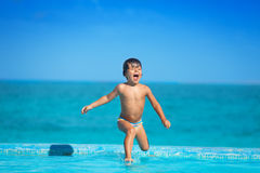 Excited kid in slow motion of jumping into  water Royalty Free Stock Image