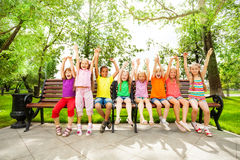 Excited kids with arms and sit in row on bench. Excited diverse looking kids, boys and girls, hold arms up straight in the air and sit in row on the bench Stock Image