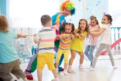 Excited kids playing tug-of-war in club. Excited kids and clown playing tug of war in club stock photo