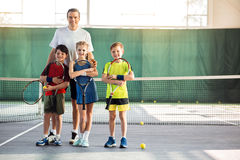 Excited kids and couch having fun on tennis court royalty free stock image