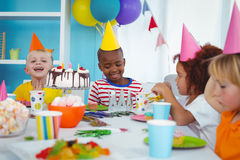 Excited kids enjoying a birthday party Stock Photography