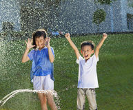 Excited kids has fun playing in water fountain Stock Photos