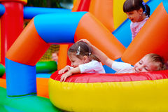 Excited kids having fun on inflatable attraction playground Royalty Free Stock Image