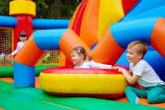 Excited kids having fun on inflatable attraction playground Stock Image