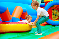 Excited kids having fun on inflatable attraction playground Stock Images