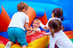Excited kids having fun on inflatable attraction playground. Group of excited kids having fun on inflatable attraction playground Stock Image