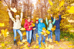Excited kids play together with flying leaves. Happy excited kids playing together with flying yellow leaves in forest during autumn daytime Royalty Free Stock Images