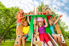 Excited kids on playground chute with arms up Royalty Free Stock Photos