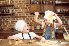 Excited kids playing with dough for shaped cookies. In kitchen Stock Photo