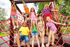 Excited kids playing together on net ropes stock image
