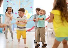 Excited kids playing tug of war in club. Group of kids play and pull rope together in day care. Games and physical activity for children royalty free stock photography